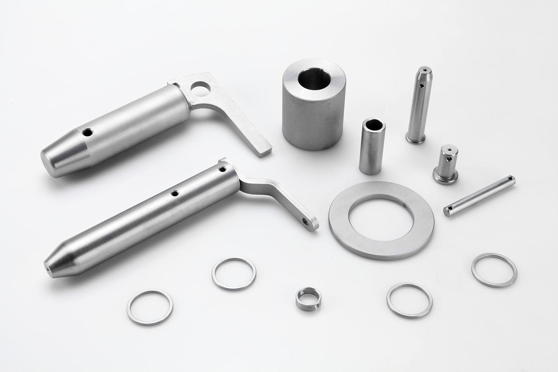 Piezas metálicas con acabado blanco, capa de zinc níquel más un pasivado transparente-irisado y sellado para aumentar la resistencia a la corrosión.